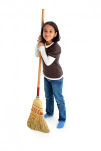 Girl cleaning the house with a broom