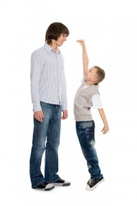Kid trying to measure up to his older brother